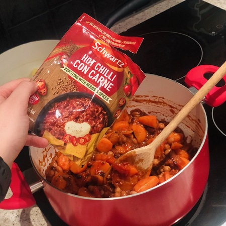 Red cooking pot with vegetarian chilli con carne with Schwartz seasoning being sprinkled in