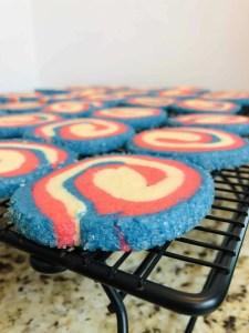 several patriotic pinwheel cookies on a cooling rack