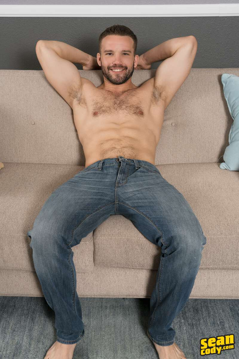 shirtless hunk sitting on a couch wearing jeans