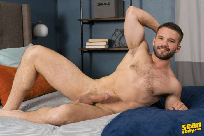 naked hairy hunk Jackson laying on a bed for the sean cody gay porn website