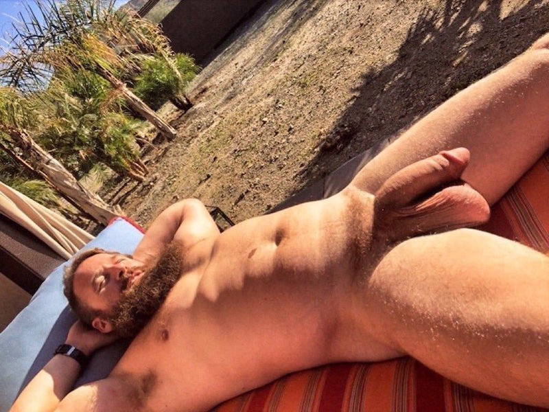 bearded man laying naked in the sun with his big cock and fat balls handing between his legs