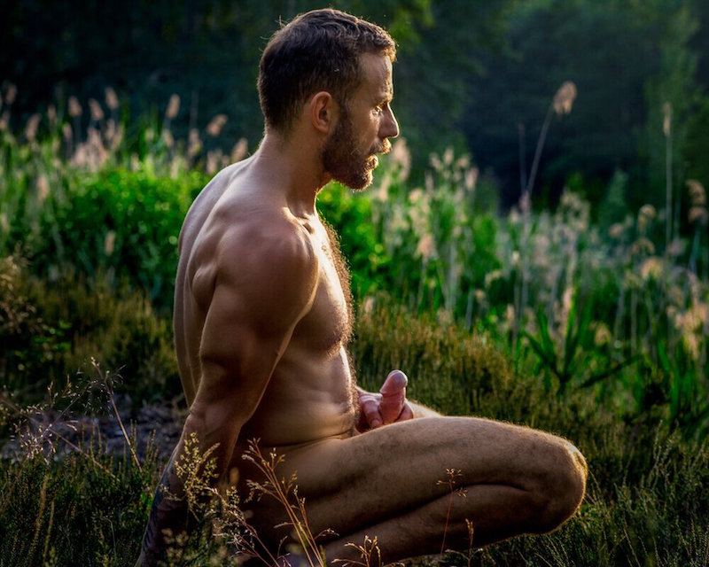 hairy man crouching naked in a meadow jacking off