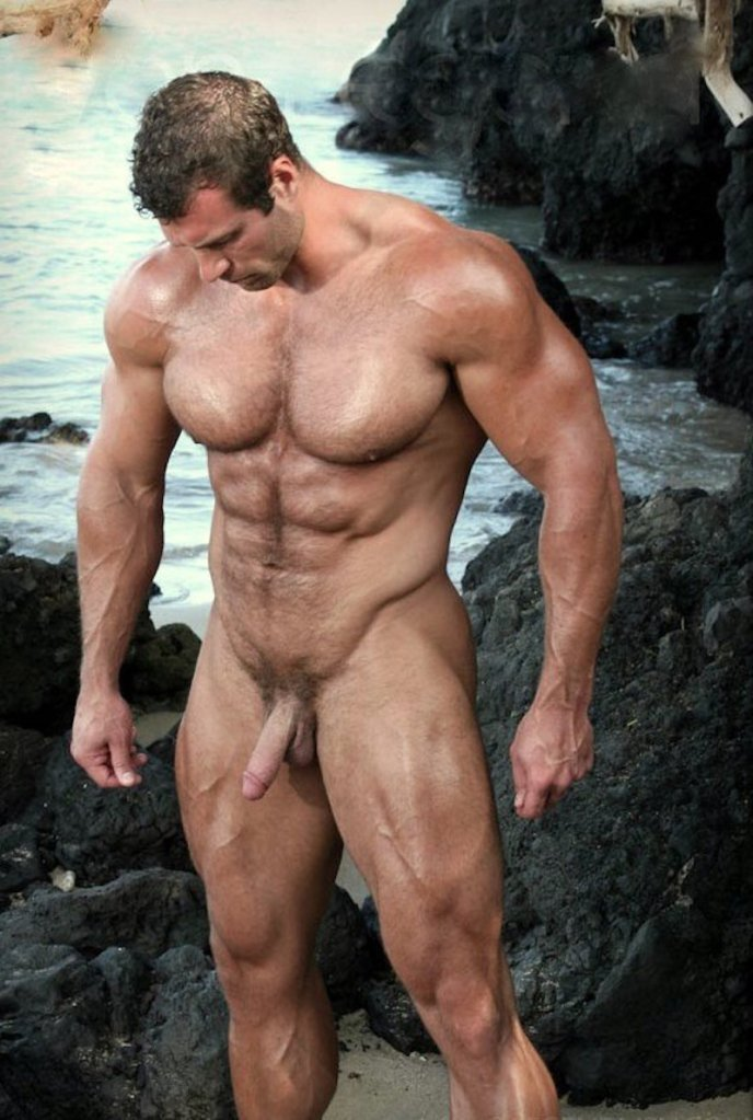 big muscle man standing naked among rocks at the beach