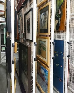 paintings hanging in storage