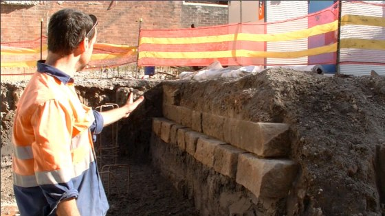 Excavation Director Tim Adams (Senior Achaeologist Umwelt) pointing out the sandstone foundations (Screen capture from Video recorded 2 April 2014)