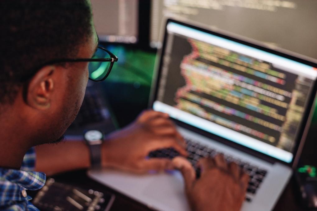 black-male-in-front-of-computer-screen-coding-mobile-app-web-development-computer-programming.jpg