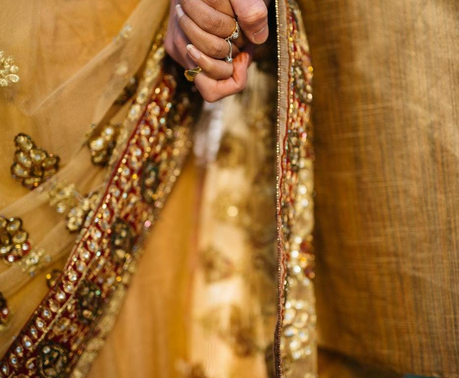 Couple holding hands wearing traditional India cloths