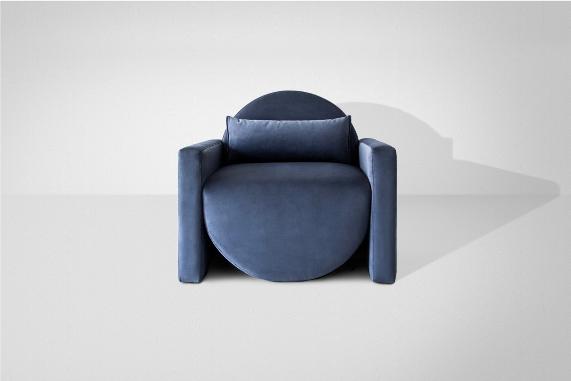 Wide and curved velvet armchair