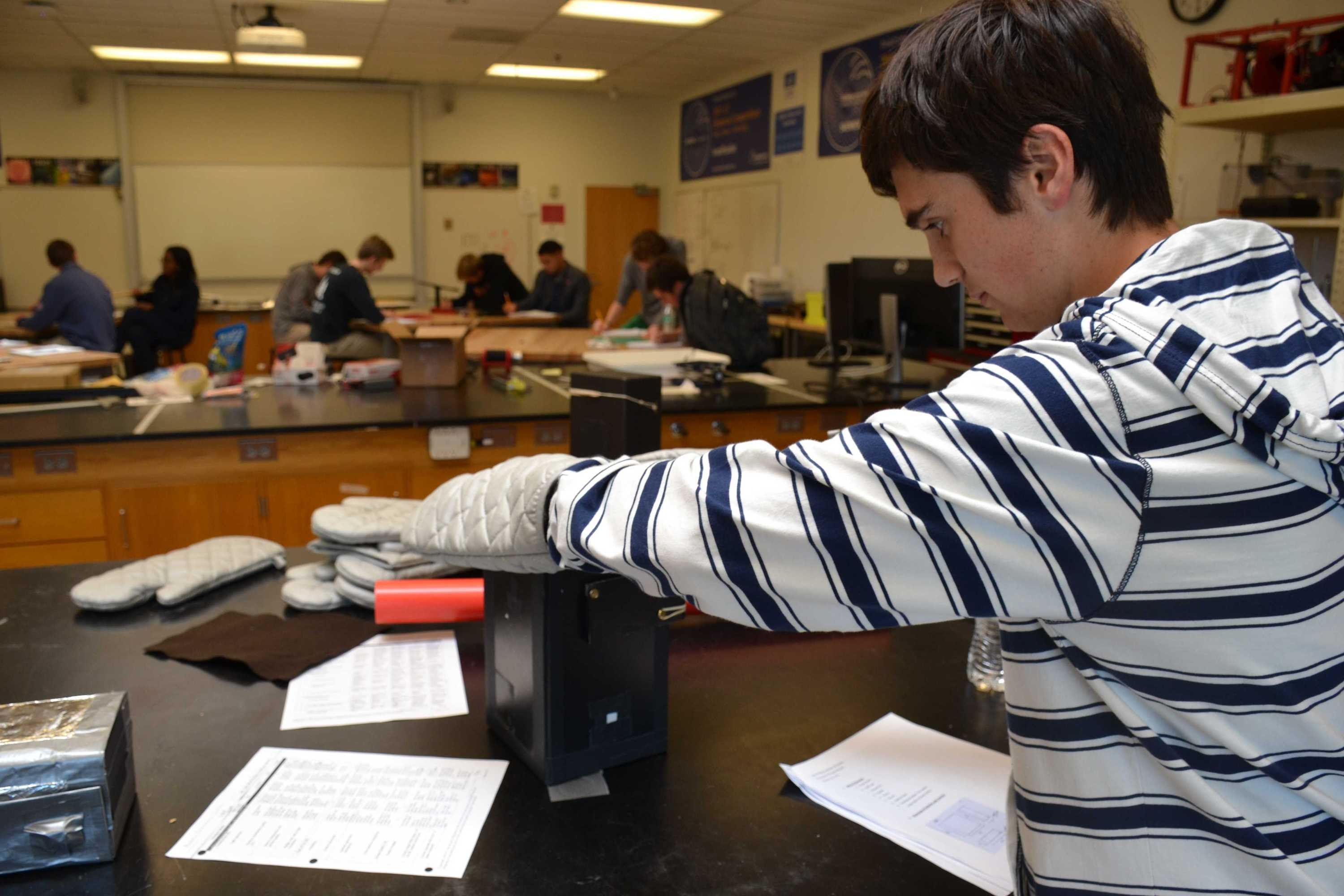 Brandon Porter '18 tests his pinhole camera during the Principles of Engineering open house Nov. 1. Students in the class designed cameras for people who have limited manual dexterity, and created manuals detailing their design process. Credit: Kaitlin Musante/Chronicle