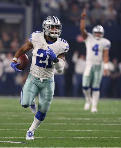Dallas Cowboys running back Ezkiel Elliott (21) runs for a first quarter touchdown run as Dak Prescott looks on as the Cowboys take on the Detroit Lions Monday, Dec. 26,2016 in AT&T Stadium in Arlington, Texas. Credit: Richard W. Rodriguez/Fort Worth Star-Telegram/TNS)