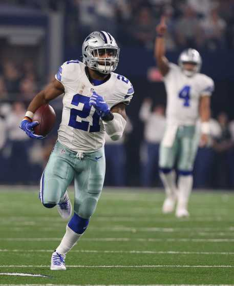 Dallas Cowboys running back Ezkiel Elliott (21) runs for a first quarter touchdown run as Dak Prescott looks on as the Cowboys take on the Detroit Lions Monday, Dec. 26,2016 in AT&T Stadium in Arlington, Texas. Credit: Richard W. Rodriguez/Fort Worth Star-Telegram/TNS)