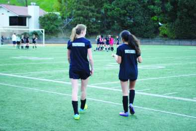 Carly Wallace '20 and Giselle Dalili '20 walk on to field during practice. Credit: Casey Kim'20/SPECTRUM