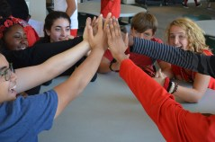 A group of 9th graders sit together at the lunch tables high fiving each other. Credit: Casey Kim '20 / SPECTRUM