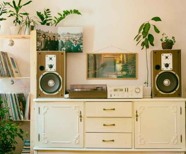 Wooden speakers with record player sitting on top of a white entertainment unit
