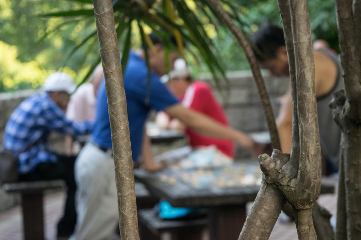 Miestni chlapi a ich oddychové odpoludnie pri hre Mahjong v Kowloon Park