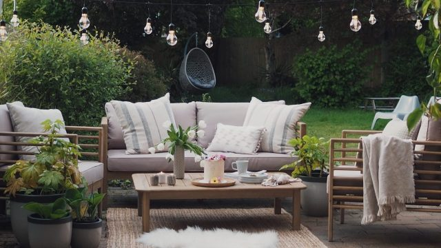 Outdoor sofa with cushions and coffee table in garden living area