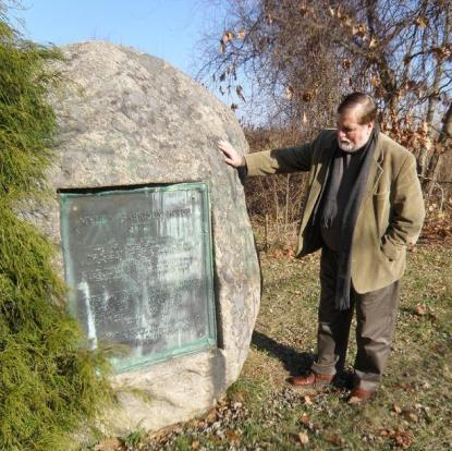 """Dr. William Brackney (co-author of Baptists in Early North America-Swansea, Massachusetts) standing at the monument near the site of John Myles' Garrison House in Swansea, Massachusetts. Location: 41° 46.37′ N, 71° 17.13′ W. Marker is at the intersection of Old Providence Road and Barneyville Road, on the left when traveling east on Old Providence Road. The text of the plaque reads: """"MYLES GARRISON HOUSE SITE Near this spot stood the John Myles Garrison House. 1st place of meeting of the troops of Massachusetts Bay and Plymouth Colonies commanded by Majors Thomas Savage and James Cudworth, who marched to the relief of Swansea at the opening of King Philip's War, A.D. 1675. There fell in Swansea, slain by the Indians, Nehemiah Allin, William Cahoone, Gershom Cobb, John Druce, John Fall, William Hammond, John Jones, Robert Jones, Joseph Lewis, John Salisbury, William Salisbury. To mark this historic site, this monument was erected by the Commonwealth of Massachusetts A.D. 1912."""" (photo credit: FBC in Swansea / Rev. C. Hartman)"""