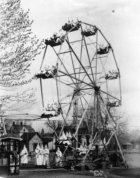 Members of Cañon City Ku Klux Klan No. 21 pose on and around the ferris wheel at the site of a carnival at 8th and Greenwood in Cañon City, Colorado. Klan members were invited by W. H. Forsythe, owner of the outfit and a klansman from Fort Collins, to don their gowns and pose for a group portrait. (photo credit: Race Relations Project)