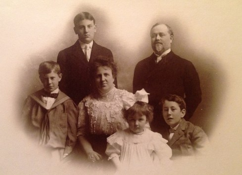 Paul Watkins family portrait (January 1907) - L to R: Roderick Henderson Watkins (1890), Paul Watkins (1864); (standing); William Benson Watkins (1898), Florence Henderson Watkins (1869), Florence Eugenie Watkins (1903), Joseph Ray Watkins (1894) (bottom row); dates are noted in a handwritten caption written by Florence Eugenie Watkins (my grandmother) on the original photo in her family album.