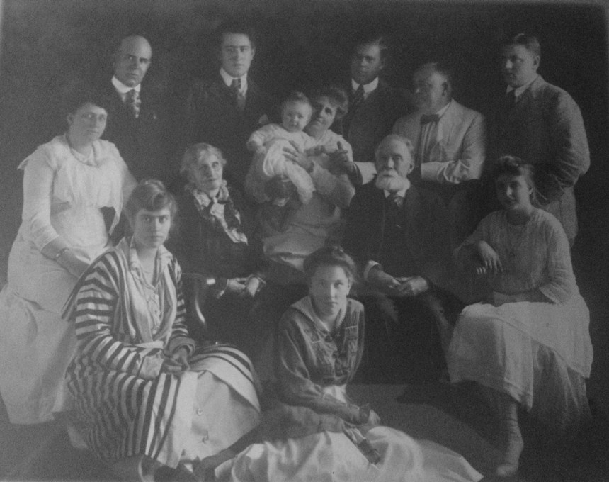 Watkins/Henderson family portrait: back row from left to right: David Elmer Henderson, Joe Watkins, William Watkins, Paul Watkins, Rod Watkins.  Middle row from left to right: Lula Henderson (Will), Elizabeth Henderson (Handley), Florence Watkins (Henderson) holding the baby of Joe and wife, Matthew Henderson, Florence Henderson (daughter of David and Lula).  Front row left to right: Helen (Slack) Watkins, Florence Watkins (from the family album of Thomas M. Smith; photo probably taken in 1916, and no later than 1917)