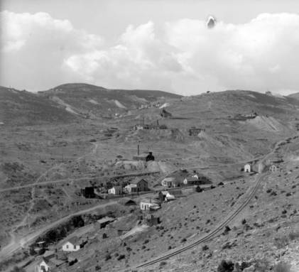 The tracks of the Gilpin Tramway curve through the foreground of this view of several mines on Gunnell Hill in Central City, Colorado. A group of houses lines this portion of Eureka Street, one of the main roads through Central City. The Gunnell Mine stands in the center background with the Whiting Mine behind it. Farther past the two mines at the base of Quartz Hill lies the small town of Nevadaville. (Denver Public Library Digital Collections, 1899?)