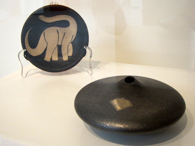 """William Andrew Pacheco, """"Black-and-white Plate (brontosaurus)"""" (1980s), native clays; Preston Duwyenie, """"Black Seed Pot with Silver Inlay"""" (n.d.), micaceous clay, silver"""