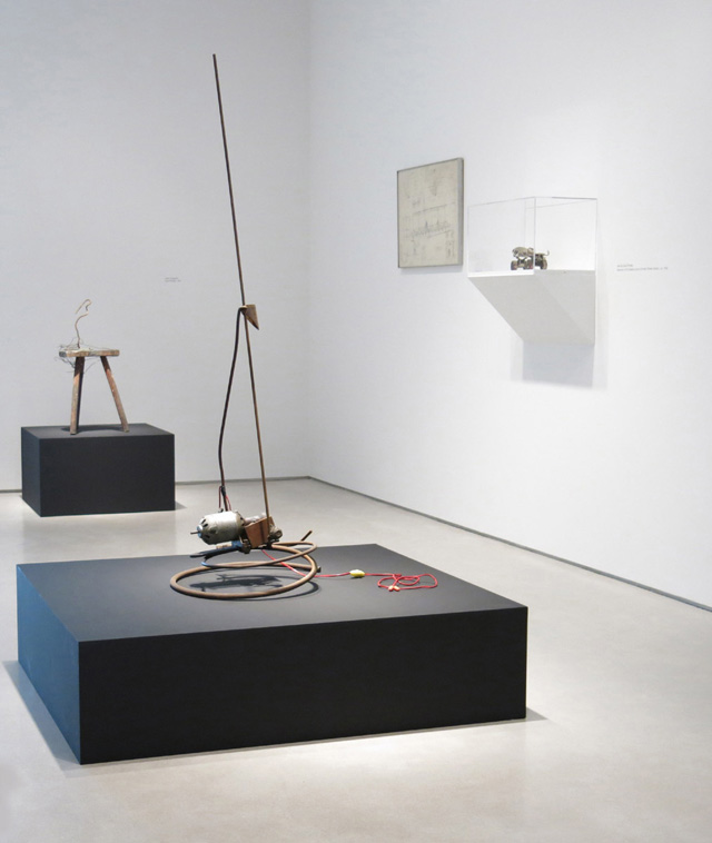 """Radio Waves"" installation view: from left, Jean Tinguely, ""Saint Phalle"" (1961), wooden stool, metal, and pigments, 28 ½ x 14 x 16 ½ inches; Jean Tinguely, ""Untitled"" (1962), metal, plastic, and electrical wire assemblage with  electric motor, 57 ½ x 20 x 18 ½ inches; Per Olof Ultvedt, ""Drawing for Project"" (1962), pencil on paper, 19 x 28 inches; Niki de Saint Phalle, ""Element of Tir tableau pour DYLABY (Roller Skate)"" (ca. 1962), painted metal and leather, 4 ¼ x 11 ¼ x 3 3/8 inches."