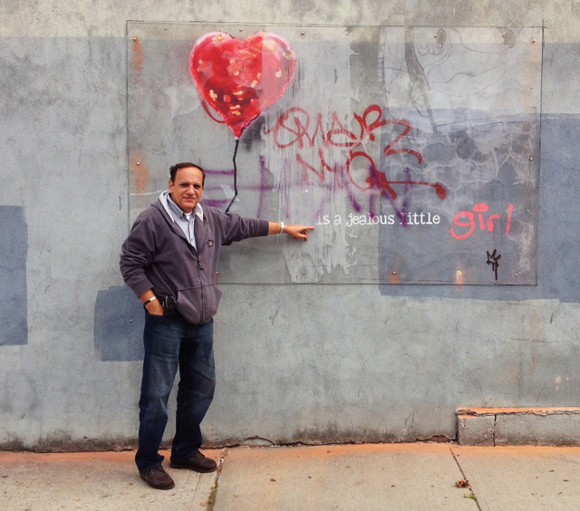 Vassilio Georgiadis with his protected Banksy in Red Hook. (photo for Hyperallergic)