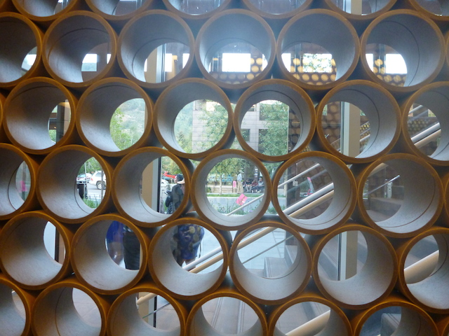 Ban's famous paper tubes gird the inside of the museum, adding texture to the view from both sides.