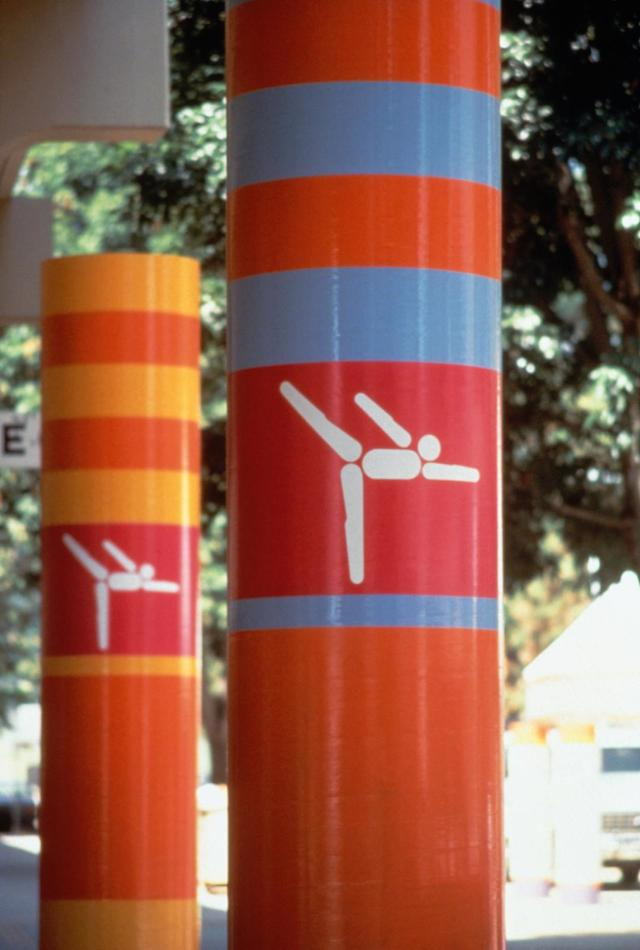 """Look of the Games"" on columns, designed by Deborah Sussman (©IOPP / Annette Del Zoppo) Los Angeles 1984 OG, Views and atmosphere of the city - Pictogram of gymnastics at the Pauley pavilion."