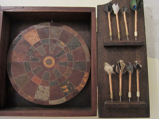 "Jackie Mock, ""Center,""a dartboard with inlaid soil from all 50 states, with the geographical center of the US as the bullseye, and darts with feathers of North American birds"