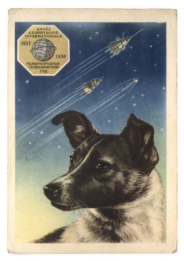 LAIKA POSTCARD Postcard, USSR (1958) A portrait of Laika by the artist E. Gundobin, with the first three Sputniks in the background. Text reads 'International Geophysical Year 1957–1958'.  © FUEL Publishing