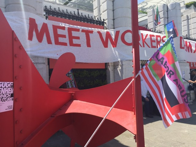 Flyers, flags, and banners outside the Peggy Guggenheim Collection and propped against an Alexander Calder sculpture