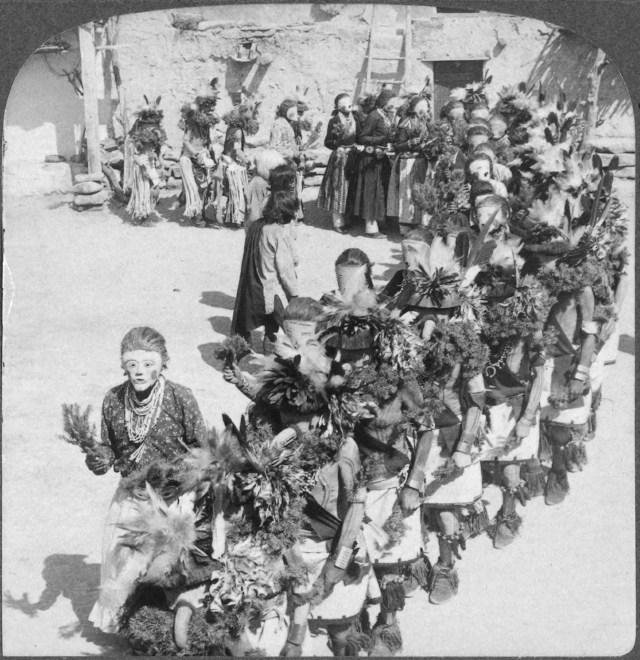Villagers in Shonghopavi, Arizona wearing Katsina masks (Image via Wikimedia)