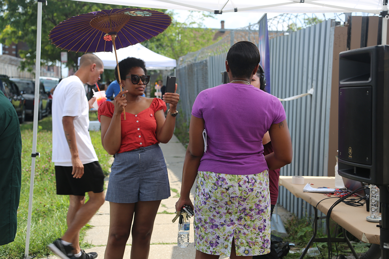 Vocalo DJ (left, with parasol) interviews CCJ warden Nneka Jones Tapia.