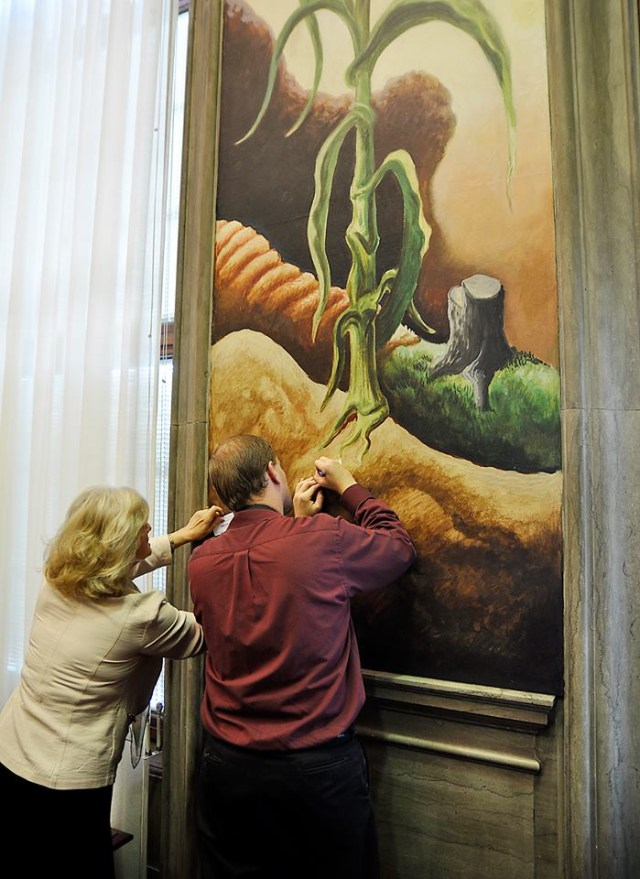 Missouri Republican Party Vice Chairwoman Valinda Freed and an unidentified man writing on business cards while leaning on the Thomas Hart Benton mural (photo by Dave Marner, via Facebook)