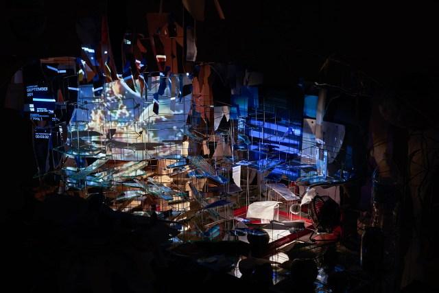 "Sarah Sze, ""Measuring Stick"" (detail) (2015), video projectors, fan, light, mirrors, wood, stone, archival prints, speakers, stainless steel, balloon, sand, fruit, egg, plastic, toilet paper, aluminum foil, grass, 132 x 90 x 51 in (335.3 x 228.6 x 129.5 cm) (photo by Mike Barnett)"