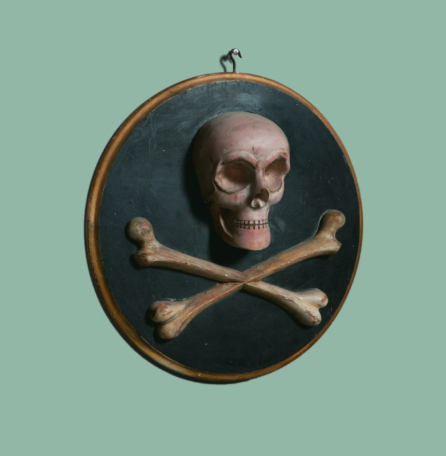 Odd Fellows skull and crossbones plaque (1870s), unknown maker, possibly M. C. Lilley & Co., carved and painted wood, 16 in. diameter (courtesy Webb Collection)