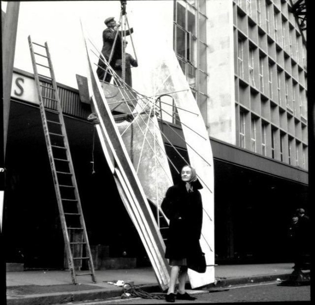 Private Public ArtInstallation of Barbara Hepworth's Winged Figure, 1961-2, Holles Street, London, with the artist looking on. The private sector was also pivotal in the creation of important works of art. Hepworth's Winged Figure which she created for the John Lewis Partnership is a key example of sculpture commissioned for commercial premises. Copyright John Lewis Partnership Archives