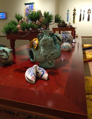 Display of ceramic works in 'Jiha Moon: Double Welcome, Most Everyone's Mad Here' at the Kalamazoo Institute of Arts