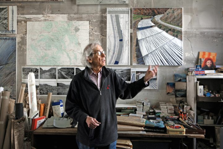"Christo in his studio with a preparatory collage for ""Over The River,"" 2011 (photo by Wolfgang Volz, © 2011 Christo)"