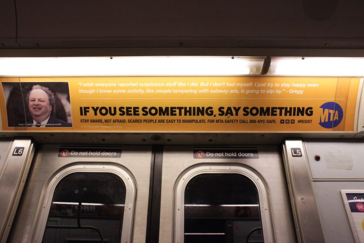 "One of the substitute MTA ads, which reads: ""I wish everyone reported suspicious packages like I did. I just try to stay happy even though I know some activity, like people tampering with subway ads, is going to slip by."""