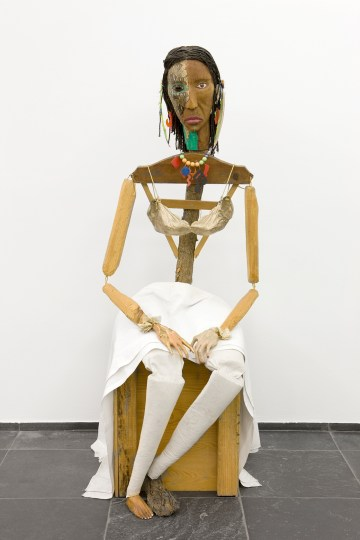 """Jimmie Durham, """"Malinche"""" (1988–92), guava, pine branches, oak, snakeskin, polyester bra soaked in acrylic resin and painted gold, watercolor, cactus leaf, canvas, cotton cloth, metal, rope, feathers, plastic jewelry, glass eye, 70 x 23 5/8 x 35 in, Stedelijk Museum voor Actuele Kunst (SMAK), Ghent, Belgium (photo © SMAK / Dirk Pauwels)"""