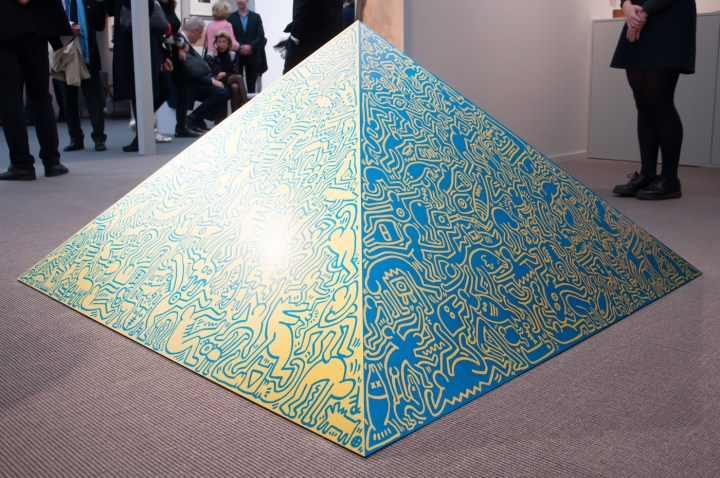 """Keith Haring, """"Pyramid Sculpture"""" (1989), aluminum, anodized, mounted on wooden plinth, 56.69 x 56.69 x 29.53 in (photo by Maria Victoria Recinto)"""