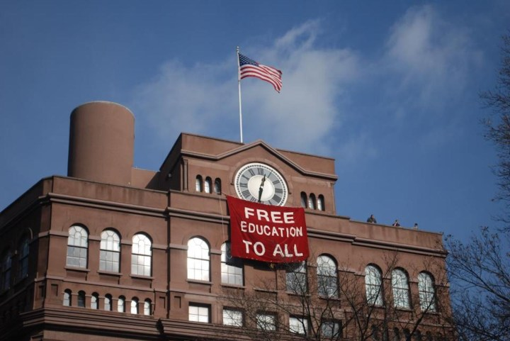 Students hang banner below the historic clock tower of the Cooper Union Foundation Building in December 2012. (photo by Free Cooper Union, via Wikimedia Commons)