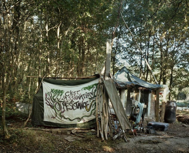 """A ZAD house with the banner that reads: """"This is a summons to resist"""" (courtesy Crimeth Inc.)"""