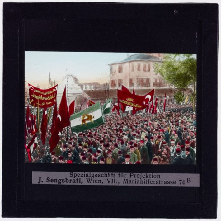 Crowd on the street with Turkish flags, 1900