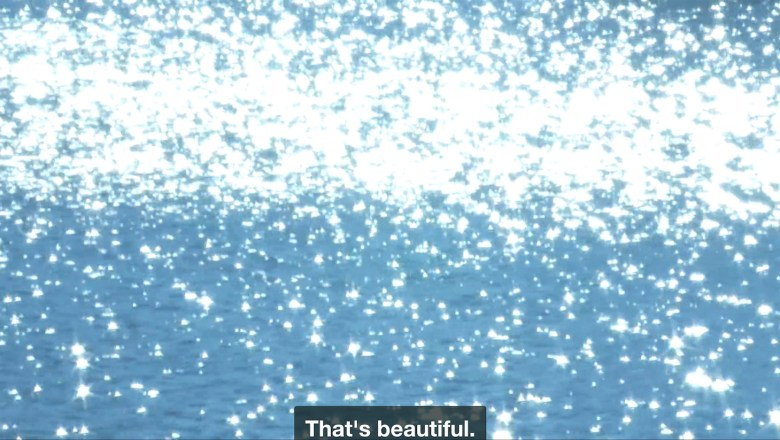 """Light glimmers on water, so bright it blots out part of the image in all white. A caption at the bottom of the screen reads: """"That's beautiful."""""""