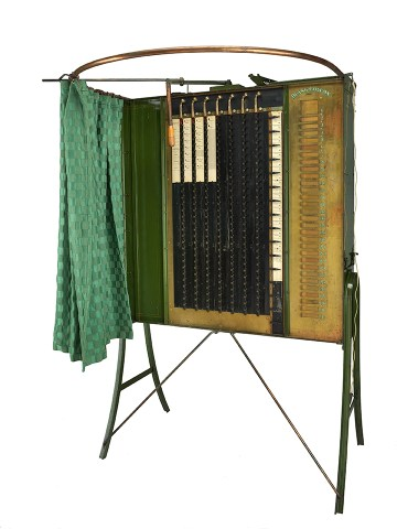An 1890s gear-and-lever voting machine with a patterned green curtain.