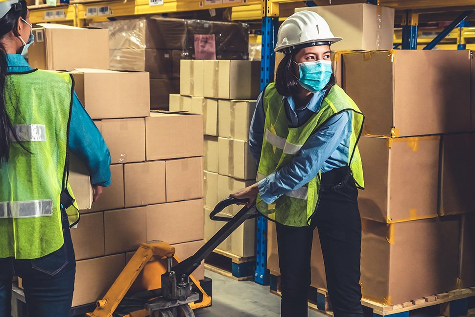 Photo : Woman moving boxes using a pallet jack a